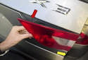 Then, remove the tail light by pulling in the inner corner out of tail gate (red arrows) and removing at an angle to unhook the outer edge (yellow arrow).
