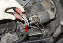 Remove the two battery cables from the starter solenoid (red arrow).