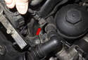 Working at the left front of the cylinder head, disconnect the VANOS solenoid electrical connector (red arrow) by pressing the wire release and pulling it straight off.
