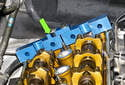 Install camshaft locking jig (11 3 240) at rear of camshafts (green arrow).