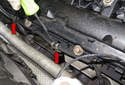 Pull the oxygen sensor wires and mounting clips (red arrows) off the valve cover.