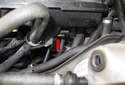 Working the left lower corner of the intake manifold (red arrow), unclip the wiring harness and any hoses that are hooked to the corner of the manifold.
