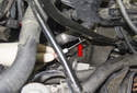 Working at the lower pipe reservoir hose connection, use a small flathead screwdriver to lever out the coolant hose retaining clip (red arrow).