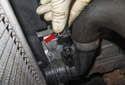 Working at the lower radiator hose, press the release (red arrow) and disconnect the outlet temperature sensor by pulling it straight off.