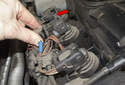 Unlock the ignition coil electrical connector (red arrow) by pulling the tab up 90 degrees (red arrow).