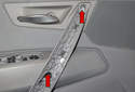 Then, remove the two door panel T30 Torx fasteners (red arrows).