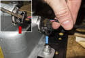 Support the door panel, then disconnect the airbag electrical connector by pulling lever out the lock (red arrow), then pulling the connector straight out (blue arrow).