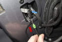 Next, pull the door handle Bowden cable down to unclip (red arrow), then unhook the top from the lever (blue arrow) and remove.