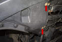 Front liner: Working at the front corner of the liner under the vehicle, remove the two 8mm fasteners (red arrows).
