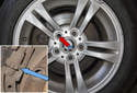 Remove one wheelbolt per rear wheel while the vehicle is on the ground.