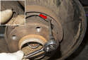 Using a long 5mm Allen bit, remove parking brake shoe retaining clips by rotating 90° and pulling away from brake shoes (inset).