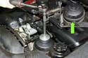"""6-cylinder engine: Using a 36mm oil filter socket on a 6"""" extension, loosen the oil filter housing lid until you can see a sealing O-ring (green arrow)."""