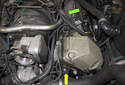 The sensor is mounted in the timing cover (yellow arrow) and the wiring harness runs up and over the timing cover to the electrical junction box (green arrow).