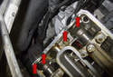 Apply RTV to the camshaft bores at the rear of each cylinder head (red arrows).