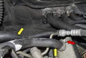 Working at the left rear of the engine, remove the oil separator hoses (yellow arrows).