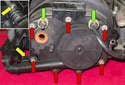 Start by removing the remaining vacuum hose or plug (green arrows).
