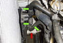 Working at the right lower side of the radiator, remove the three hoses from the automatic transmission cooler (red arrow) bracket (green arrows).