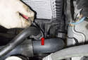 Use a flathead screwdriver to lever out the coolant hose retaining clip (red arrow).