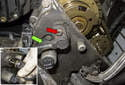 Working at the front of the timing cover, remove the 5mm camshaft sensor-mounting fastener (red arrow).