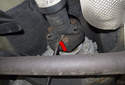 Next, use a pry bar to lever the driveshaft away from the flex-disc (red arrow).