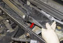 At the sides of the cabin filter housing, slide the drain channel up (red arrow) and remove it.