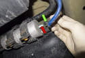 Working at the fuel pump, remove the vacuum line by pulling it straight off (green arrow).