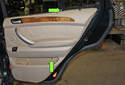 Remove the two T20 Torx door panel screws (green arrows).