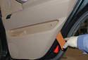 Using a plastic pry tool, insert it between the door panel and door.