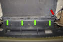 Working at the center bottom of the rear bumper, between the mufflers, lever the retaining tabs (green arrows) out with a flathead screwdriver (red arrow).