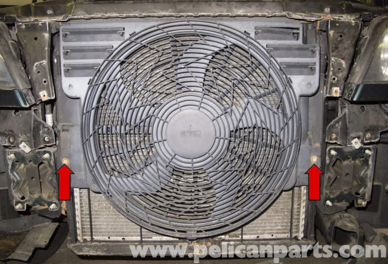 working on the sides of the cooling fan, remove the two 10mm fasteners (red
