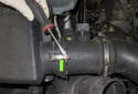 Using a flathead screwdriver, unclip the top spring clip (green arrow) that holds the mass air flow sensor into the air filter housing lid.