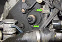 Right Side Seal: Remove the two 10mm VANOS seal fasteners (green arrows).