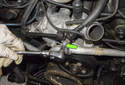 Working at the front top of the water pump, remove the 5mm Allen fasteners (green arrow).