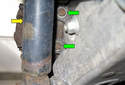Working behind the brake caliper, remove the two 16mm brake caliper bracket mounting bolts (green arrows).