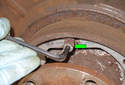 Using a long 5mm Allen wrench, remove the parking brake shoe retaining clips by rotating it 90° and pulling it away from the brake shoes.