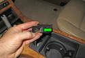 Next, pull the hazard switch out of the console and remove the wiring harness (green arrow).
