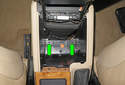 Working inside the cavity for the storage bin, remove the two console mounting screws (green arrows) with a Phillips screwdriver.