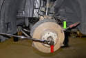 Remove the axle nut using a 36mm 12-point socket and a ratchet (red arrow).