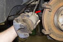 Remove the brake caliper from the mounting bracket and unscrew the brake hose from the caliper.