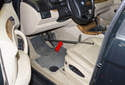 Depress the brake pedal half way and hold it in place with a stick or brake pedal depressing tool (red arrow).