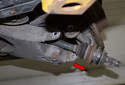 As you drive the axle out of the wheel hub, guide it down (red arrow) and remove it from the vehicle.