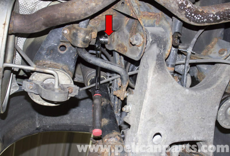 working at the rear of the control arm, counterhold the 18mm nut (red arrow