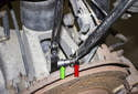 Loosen the 21mm nut (red arrow) while counter-holding the 10mm hex boss (green arrow) on the ball joint.