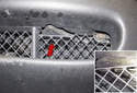 Working through the front bumper grille, use a trim panel tool to lever out the center plastic rivet (red arrow).