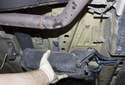 Slowly lower and guide the charcoal canister out of the rear fender and remove it from the vehicle.