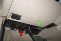 The red arrow points to the plastic panel above the pedal assembly.