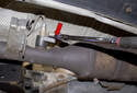 Replacing sensor after catalytic converter: Using an oxygen sensor socket (red arrow), loosen the oxygen sensor connection to the exhaust pipe.