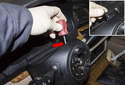 Working at the top of the steering column trim panel, remove the plastic Phillips head screw (red arrow).