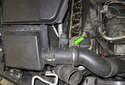 Working at the mass airflow sensor, loosen the hose clamp using a flathead screwdriver (green arrow).