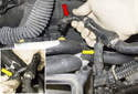 Once out, lift the brake booster vacuum hose (red arrow) up, then separate the junction (yellow arrows).